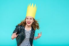 Party girl in leather jacket and party crown on pastel blue background celebrating and dancing. Party, fun, dancing, laughing. Party girl in leather jacket and royalty free stock photo