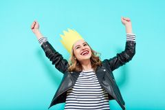 Party girl in leather jacket and party crown on pastel blue background celebrating and dancing. Party, having fun. Royalty Free Stock Image