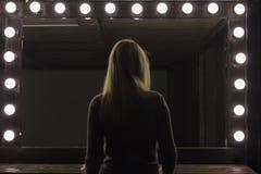 Party girl que está na frente de um espelho, foto de stock
