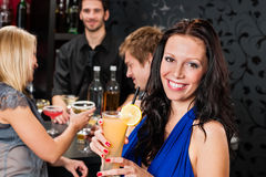 Party girl smiling with friends at bar Stock Photos