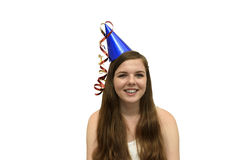 Party Girl. Smiling, young woman wearing a blue party hat with red and gold streamers isolated on a white background stock photography