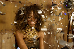 Party girl. Surprised young african american woman in gold makeup and accessories stretching out hands while confetti falling on. Party girl. Surprised young stock photography