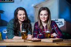 Party girls. Beautiful girls drinking beer in bar. Girls friends toasting and eating in the pub. Party girls. Beautiful girls drinking beer in bar. Girls Royalty Free Stock Photography
