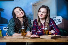 Party girls. Beautiful girls drinking beer in bar. Girls friends toasting and eating in the pub. Party girls. Beautiful girls drinking beer in bar. Girls Royalty Free Stock Images