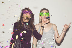 Party girls. Two girl friends having fun, dancing and making crazy faces while taking photos at a party Stock Photos