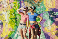 Party girls. Two young girls stand in the background of graffiti and look out for something. Party girls. Teenagers Royalty Free Stock Images