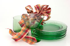 Party glassware & ribbons in green, golds,red. Royalty Free Stock Photo