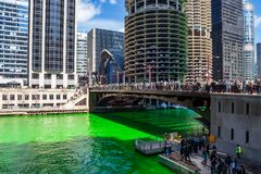 Party-goers gather on a bridge over a dyed green Chicago River royalty free stock photography
