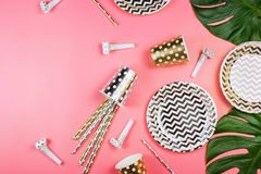 Party golden and silver paper glasses, dishes and straws, party horns and monstera leaves on a table. Pink background. Party concept Stock Photos