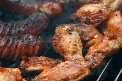Party grill. Chicken meat and sausage grilled on barbecue Stock Images