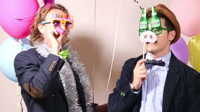 Party guys having fun with funny props in photo booth stock video footage