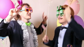 Party guys in photo booth. Happy party guys dancing in photo booth stock video
