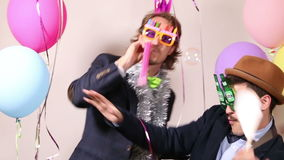 Party guys in photo booth. Happy party guys dancing in photo booth stock footage