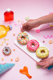 Party. Hand holding plate of colourful sugary round glazed donut Royalty Free Stock Images