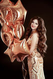 Party. Happy brunette girl with golden star balloons wears in el. Egant dress isolated on black studio background.  holiday, birthday concept Royalty Free Stock Photo