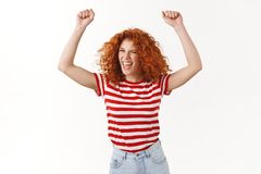 Party hard go wild. Excited carefree redhead sassy curly-haired woman jumping dancing having fun yelling singing along. Enjoy music band concert raise hands stock photo
