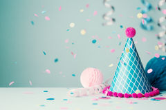 Party hat and falling confetti. Colorful party hat with confetti and streamers royalty free stock photo