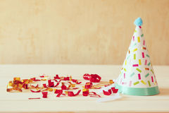 Party hat next to colorful confetti on wooden table. Royalty Free Stock Image