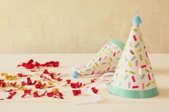 Party hat next to colorful confetti on wooden table Royalty Free Stock Photo