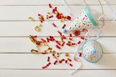 Party hat next to colorful confetti on wooden table Royalty Free Stock Image