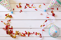 Party hat next to colorful confetti on wooden table Royalty Free Stock Images