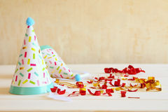 Party hat next to colorful confetti on wooden table Royalty Free Stock Photos