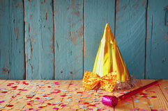 Party hat next to pink party whistle on wooden table with colorful confetti. vintage filtered image Stock Photo