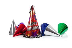 Party hats on a white background. Red, silver, green and blue party hats on a white background stock photo