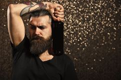 Party, holidays celebration. Bearded man with bottle on bokeh background. Tattoo, fashion, style concept. Hipster with long beard in black tshirt hold wine stock photos