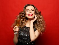 Beautiful girl in a cocktail dress with evening make-up and curls holding a glass of champagne. Party and holidays concept.Beautiful girl in a cocktail dress royalty free stock photos