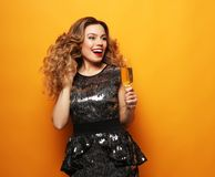 Beautiful girl in a cocktail dress with evening make-up and curls holding a glass of champagne. Party and holidays concept.Beautiful girl in a cocktail dress royalty free stock photo