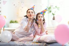 Party at home. Funny time. Mom and her child daughter are playing at home. Girls are throwing confetti. Family holiday and togetherness royalty free stock photos