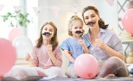 Party at home. Funny time. Mom and her children daughters are playing at home. Cute girls are holding paper mustache on stick. Family holiday and togetherness stock photography