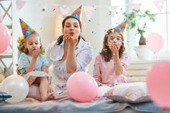 Party at home. Funny time. Mom and her children daughters are playing at home. Girls are throwing confetti. Family holiday and togetherness royalty free stock photo