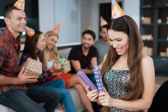 Party in honor of the birthday. The birthday girl opens the gift. She is glad to receive a gift. Royalty Free Stock Photos