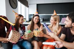 Party in honor of the birthday. Guests give their gifts to the birthday girl. The girl is very happy to receive gifts. Royalty Free Stock Photo