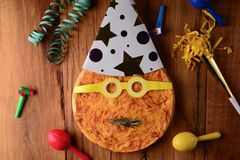 Party horns around funny pizza on tabletop royalty free stock photo