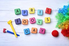 Party horns, cubes and rainbow wig. On wooden background. April fool`s day celebration Royalty Free Stock Images