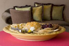 Party Hors D'eouvres. An appetizer platter of brie, other cheeses, fruits, breads and crackers with a sofa in the background Stock Photos