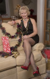 Party hostess wearing a little black revealing dress. Elderly female party hostess sitting on a sofa with a glsss of wine Royalty Free Stock Photo