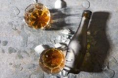 Party il tempo Bevande e bottiglia dell'alcool con brandy, pezzi di ghiaccio sulla tavola grigia fotografie stock