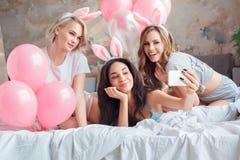 Party Junge Frauen, die zusammen Häschenohren zu Hause auf Bett mit den Ballonen nehmen selfie auf dem Smartphonelächeln glücklic lizenzfreies stockbild