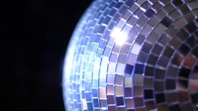 Party Light music disco ball changing hue on black background. Rotating sparkling mirror disco ball rotating in nightclub lights,. Festive party atmosphere, fun stock footage