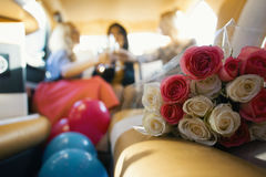 Party in limousine - happy girls celebrating, women drinks champagne - in front of bouquet of roses. Close up Royalty Free Stock Photography