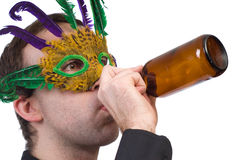 Party Man. Closeup view of a man wearing a feather mask drinking from a beer bottle, isolated against a white background Stock Image