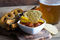 Party mix tortilla chips, pile of bread sticks and pretzels and glass of beer Royalty Free Stock Image