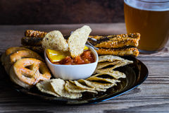 Party mix tortilla chips, pile of bread sticks and pretzels and glass of beer Royalty Free Stock Photo