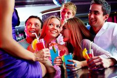 Party moment. Photo of pretty girls and guys looking at one of their friends sitting on the bar stock photo