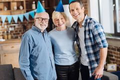Happy family posing in party hats during birthday celebration. Party mood. Pleasant young men and his elderly parents posing for the camera in the living room stock images