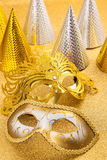 Party motive with carnival mask and party hat. In golden tone
